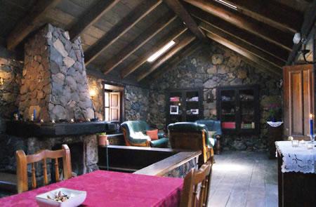 Vista salón de estar con televisión, pequeña biblioteca y rinconcito con tienda de productos locales, artesanía y souvenir.